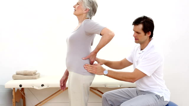 Fisioterapeuta tocar sênior doentes lombar - vídeo