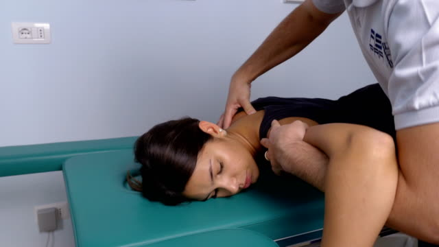 physiotherapist working on  the patient's shoulder - physical therapy стоковые видео и кадры b-roll