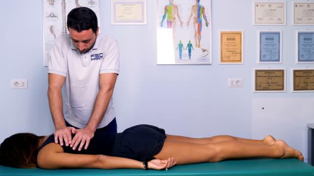 vidéos et rushes de séance de physiothérapie: physiothérapeute masser le dos du patient - chiropracteur