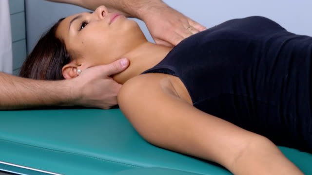 physiotherapy session: workin on patient's neck - physical therapy стоковые видео и кадры b-roll