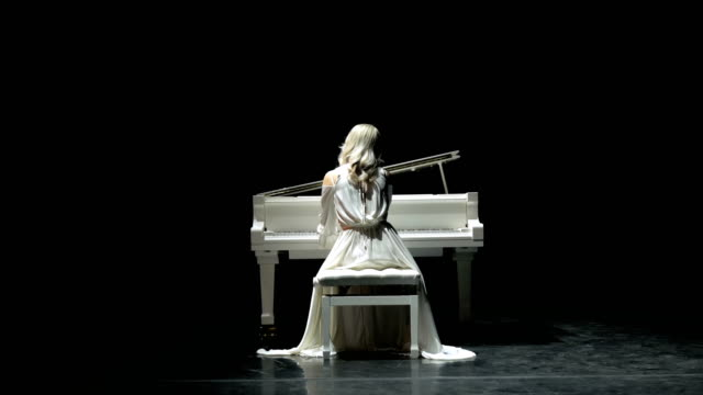 Pianist plays beautiful white grand piano on stage in concert . View from the back.