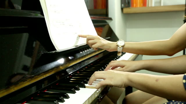 Pianist teacher teaching and playing music video