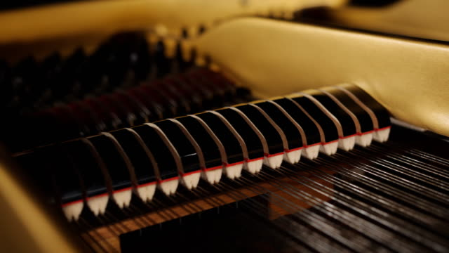 Piano hammers playing keys closeup, music background.