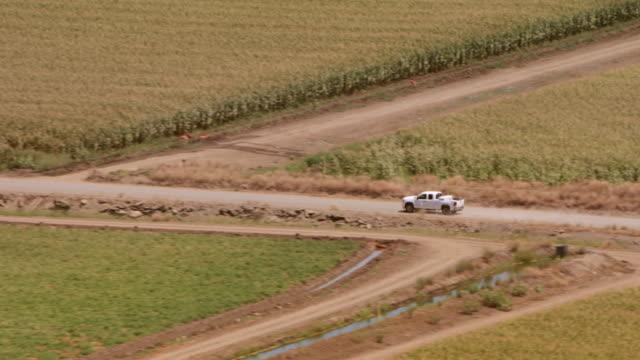 vídeos de stock, filmes e b-roll de aerial pick-up caminhão andando em uma estrada no meio dos campos na zona rural - caminhonete pickup