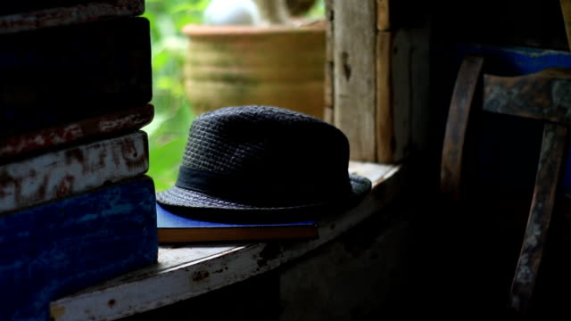 pick vintage hat and old book on the window architrave