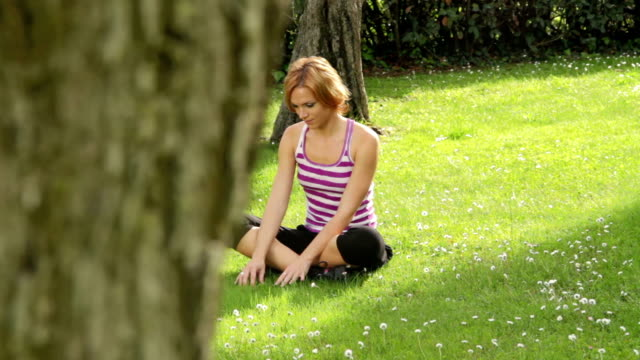 Picking flowers A young woman sitting in the grass and picking flowers. Dolly shot. side lit stock videos & royalty-free footage