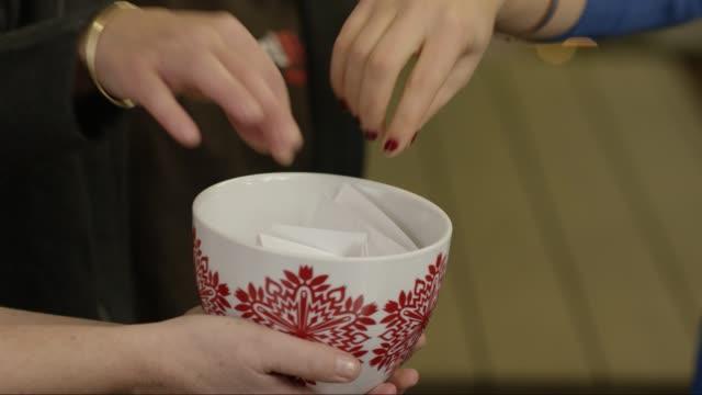 plocka från en holiday bowl - en hemlig tomte? - lotteri bildbanksvideor och videomaterial från bakom kulisserna