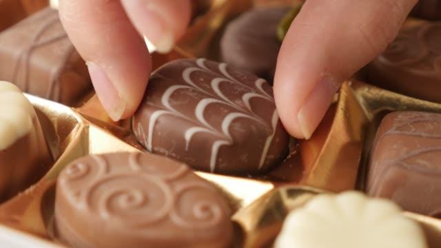 豪華なチョコレートの箱から 1 つピッキング ミックス 4 k 2160 p 30 fps ultrahd 映像 - 各種お菓子おいしいの 1 つ 3840 x 2160 uhd ビデオを選択するパックと女性の手 - バレンタイン チョコ点の映像素材/bロール
