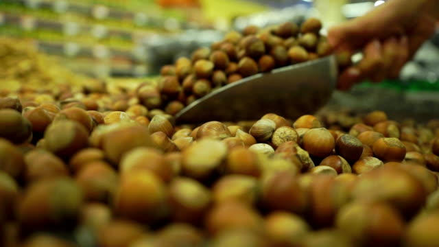 Picking some hazelnuts with a scoop in supermarket Picking some hazelnuts with a scoop in supermarket clip handful stock videos & royalty-free footage