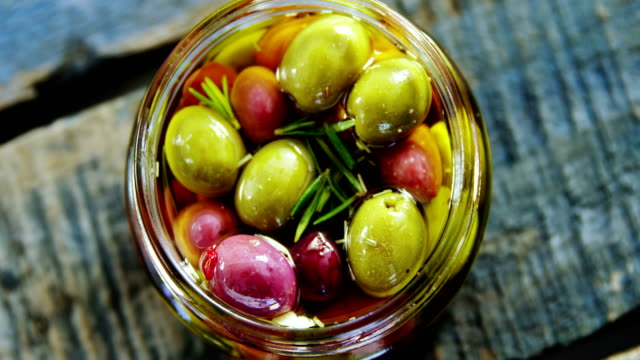 pickled olives and herbs in a jar - oliva video stock e b–roll