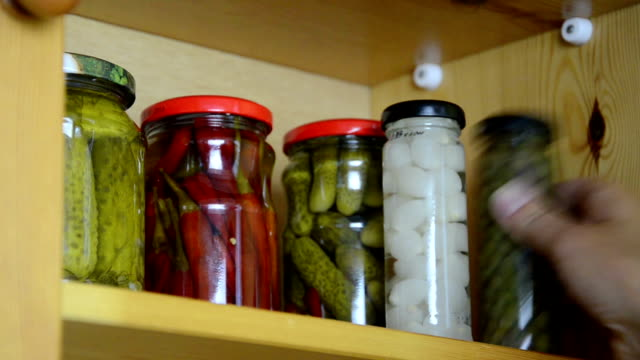 pickled vegetable jars hand takes three small jars of pickled onions garlic and capers from the shelf cabinet stock videos & royalty-free footage