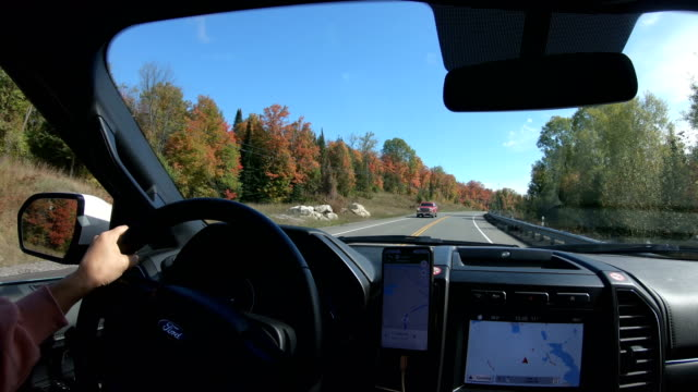 Pickup on countryside road with autumn colors and trees - video