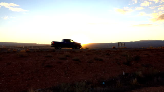 CLOSE UP: Pickup truck driving along the highway through the desert at sunset