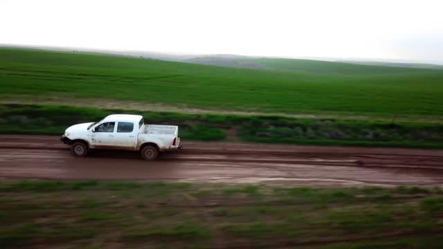 pickup truck driving in muddy fields - wiejska droga filmów i materiałów b-roll