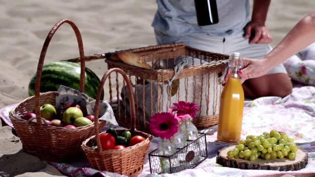 Picnic basket on colorful blanket on the beach Picnic basket on colorful blanket on the beach and wooden basket with fruits and vegetables. Closeup of man's hand taking out bottles of juice and wine, crystal glasses of picnic basket picnic stock videos & royalty-free footage