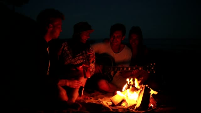 Picnic of young people with bonfire on the beach in the evening. Cheerful friends singing songs and playing guitar. Slowmotion shot - video