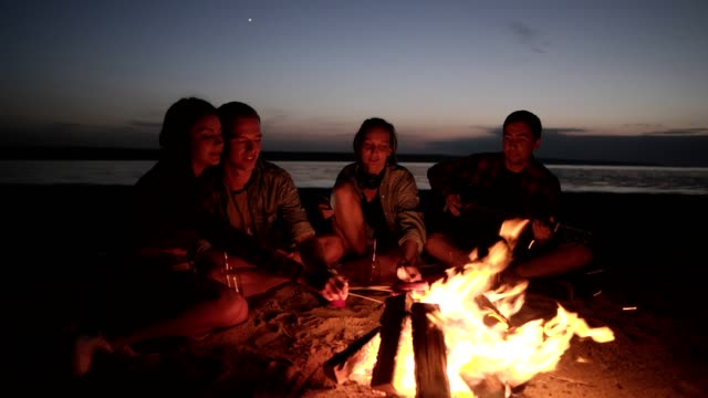 picnic with friend on the beach near the bonfire.young people are roasting sausages on wooden sticks. male from the side is playing the guitar. night time - falò spiaggia video stock e b–roll