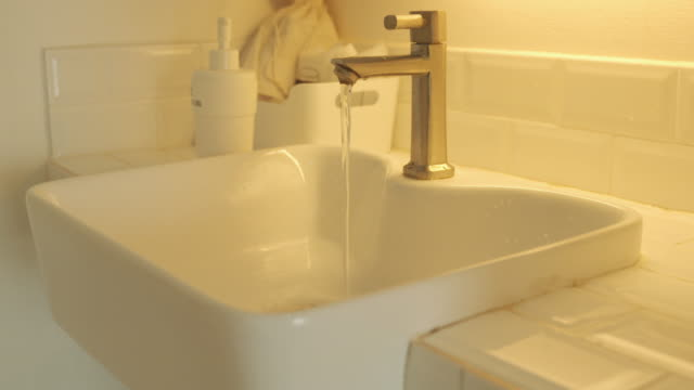Picture of a basin faucet with water left open Concept of using water resources to save the world