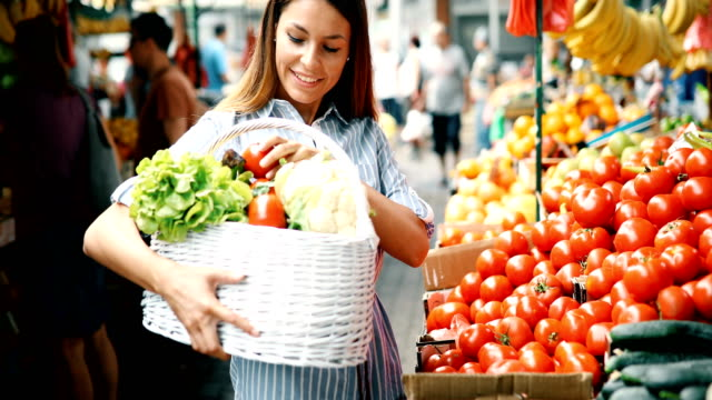 Picture of woman at marketplace buying vegetables video