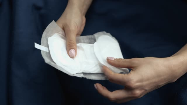 picture of woman's hand holding female gasket for hygeine. semi opened. hold with both hands. menstruation and pms period. - kobiecość filmów i materiałów b-roll