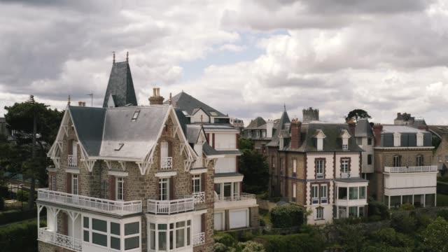灰色の曇った空に対して夏の郊外に位置する素晴らしいファッショナブルなヨーロッパのコテージの絵のように美しい航空写真。アクション。美しいヨーロッパ建築 ビデオ