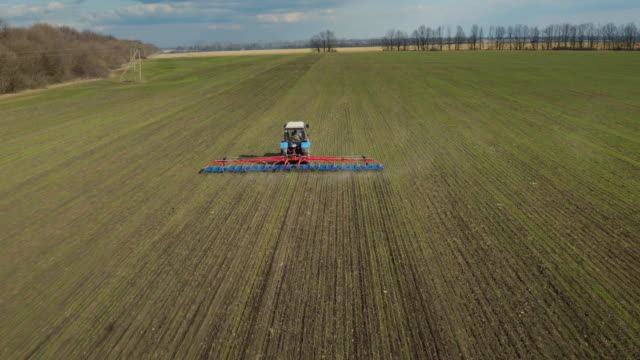 A picturesque landscape - a tractor in the field in the spring cultivates the earth. Sunny day, blue not about with clouds video