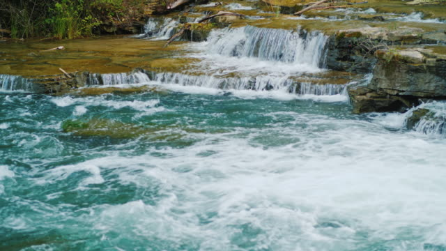 A picturesque tributary of the Niagara River, the water flows through the rocks and rapids. A beautiful mountain river video