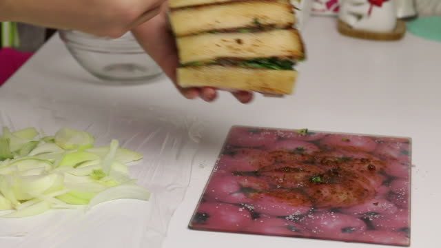 A piece of bacon, cut into an accordion. Filled with parsley and adjika. The woman puts it on a chopped onion. Salted lard with herbs and spices..mov
