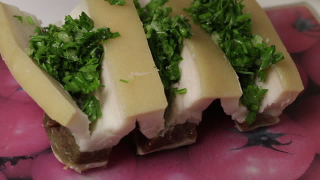 A piece of bacon, cut into an accordion. The woman puts parsley and garlic in it. Salted lard with herbs and spices.