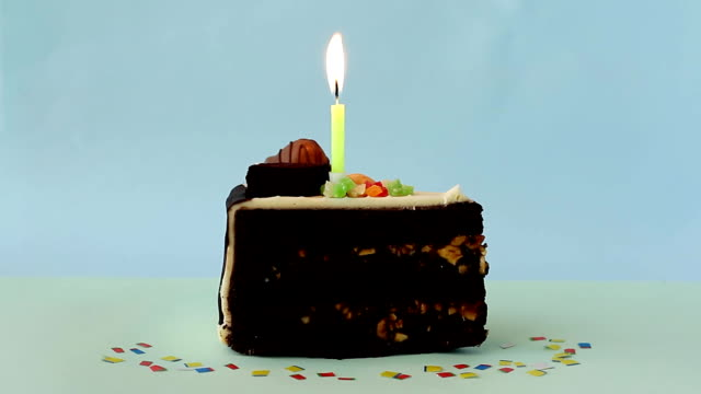 Piece of birthday chocolate cake with burning candle on blue background. Happy Birthday!
