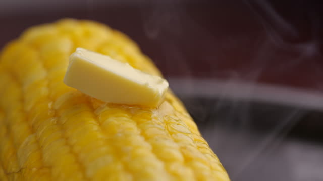 vídeos de stock e filmes b-roll de piece of butter melting on hot corn with smoke. close-up of tasty sweet corn. 4k slow motion video - comida pronta