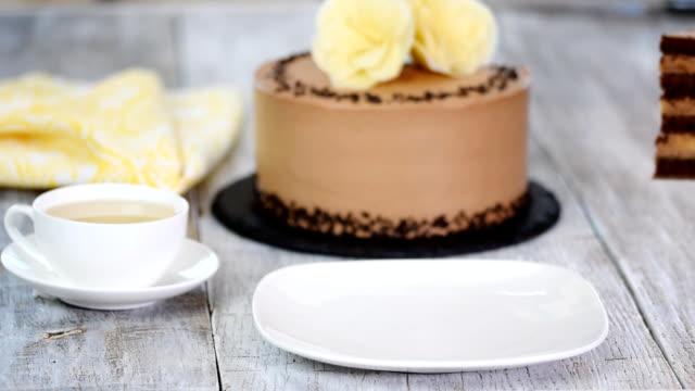 ahşap beyaz bir tabak üzerinde çikolatalı kek parçası. - kek dilimi stok videoları ve detay görüntü çekimi