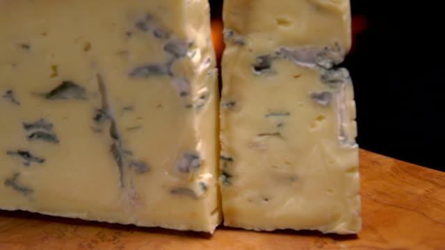 stück köstlichen blauen roquefort-käse fällt auf das brett - brie stock-videos und b-roll-filmmaterial