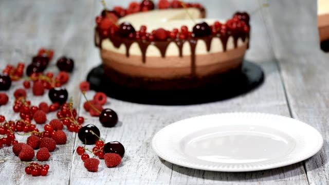 vídeos y material grabado en eventos de stock de pedazo de delicioso pastel de tres mousse de chocolate decorado con bayas frescas. - suflé