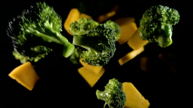 A piece of pumpkin with broccoli isolated on a black background top view. Slow motion Close up piece of pumpkin with broccoli isolated on a black background top view. Slow motion competition group stock videos & royalty-free footage