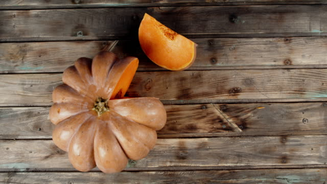 a piece of ripe pumpkin on the table. - zucca video stock e b–roll