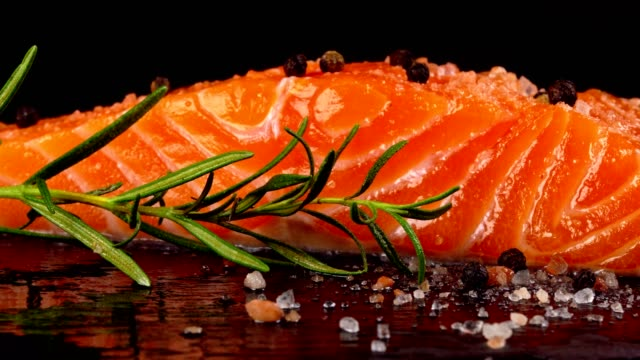 vídeos de stock e filmes b-roll de piece of salmon fillet with spices, ready for salting. - meat plate