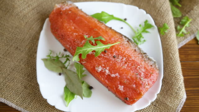 piece of salty red fish with different seasonings and herbs in a plate video