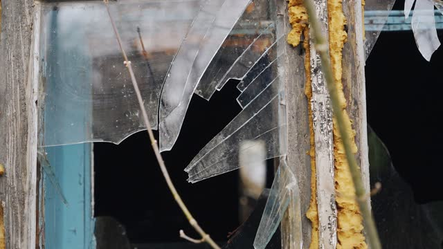 A piece of slate falls into the old window chipping a piece of glass. Shooting in slow motion