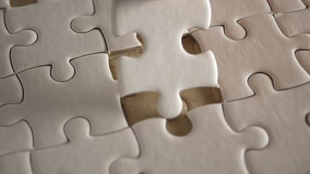 Piece of white jigsaw filling by hand, Success concept - video
