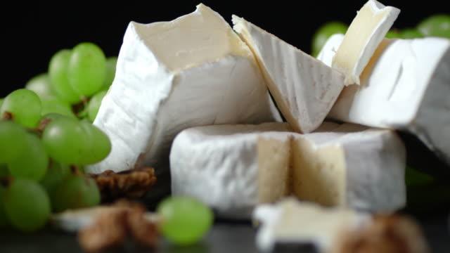 pieces of camembert cheese with grapes slowly rotating. - francuska kuchnia filmów i materiałów b-roll