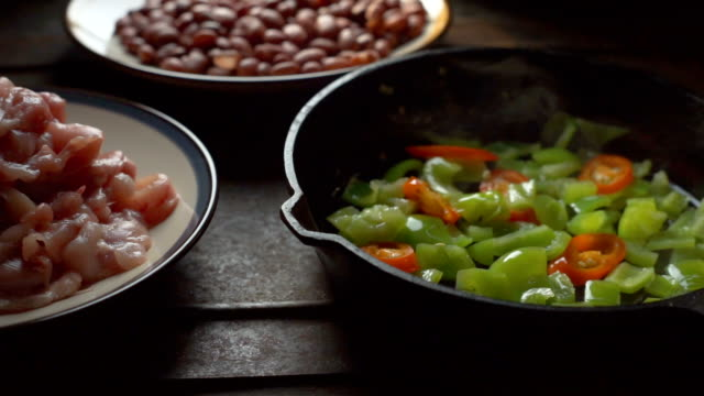 Pieces of chicken, beans. Green pepper and chili in a frying pan. Video video