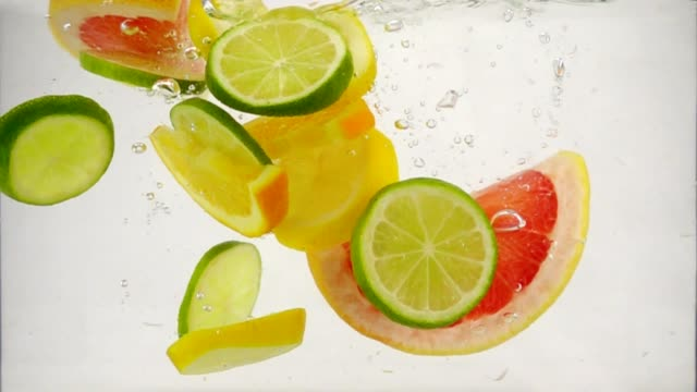 Pieces of citrus fruits lime, lemon, orange, grapefruit fall into the water with splashes and bubbles, slow motion close-up