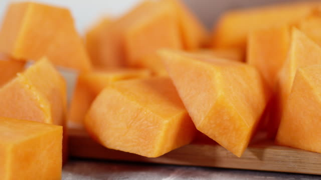 pieces of fresh pumpkin on the cutting board slowly rotate. - zucca video stock e b–roll