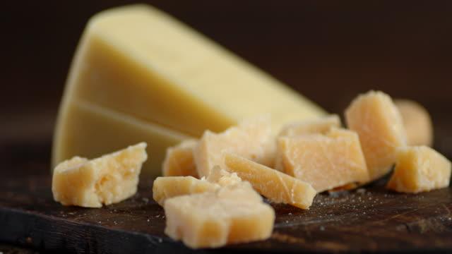 vidéos et rushes de des morceaux de parmesan tombent sur une planche à découper. - aliment en portion