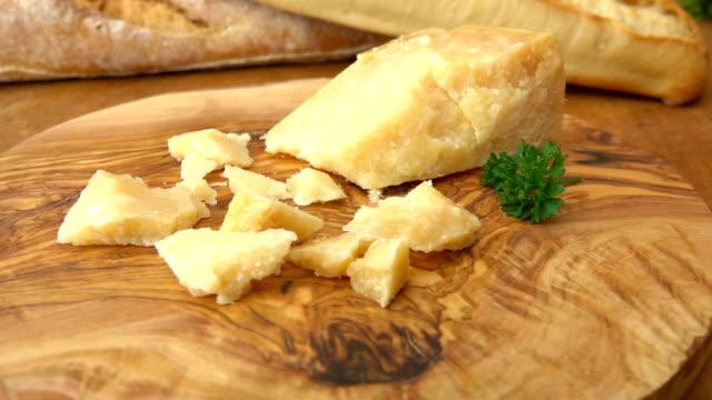 vidéos et rushes de morceaux de parmesan sur la surface en bois - parmesan