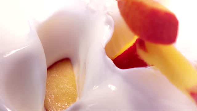 pieces of peach falling into yogurt in real slow motion video