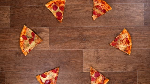 pieces of pizza are separated and moved away in different directions and then collected, stop motion animation - pizza filmów i materiałów b-roll