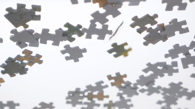 Pieces of puzzle falling down. Conceptual. Multitasking concept. Part of whole product. Task and subtasks. White back with falling down objects, small pieces. Lots of tasks to do Puzzle pieces falling down. Glass transparent background. Business concept. Background from different aspect. Pieces of jigsaw puzzle fall down on transparent surface. View from below. Multitasking part of stock videos & royalty-free footage