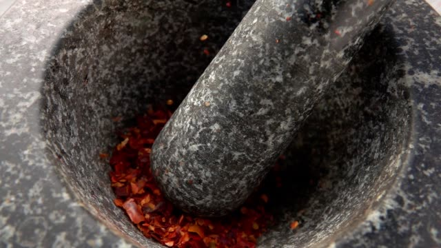 pieces of red hot chilli pepper are falling into the stone mortar - paprica video stock e b–roll